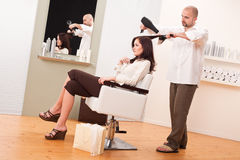 Professional hairdresser with hair dryer at salon Stock Photo