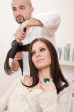 Professional hairdresser with hair dryer at salon Stock Photography