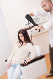 Professional hairdresser with hair dryer at salon Stock Photos