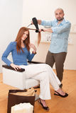 Professional hairdresser with hair dryer at salon Royalty Free Stock Photography