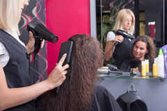 Professional hairdresser with hairdryer and hairbrush drying fem. Ale hair in beauty salon stock photos
