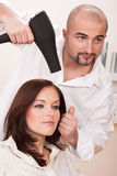 Professional hairdresser with hairdryer at salon Royalty Free Stock Images