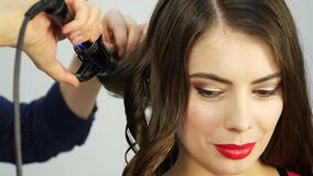 Professional hairdresser make curls, uses curling rod. fashion industry cosmetics. stock video