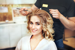 Professional hairdresser makes hairstyle for a long hair model Stock Photography