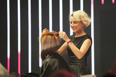 Professional hairdresser making stylish haircut on a stage royalty free stock images