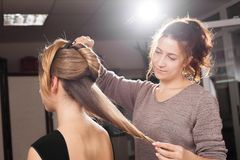 Hairdresser making a coiffure with a bun to a model stock photo