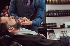 Professional hairdresser modeling beard with scissors and comb at the barbershop. Bearded male sitting in an armchair in a barber shop while hairdresser stock photography