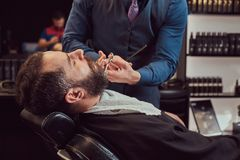 Professional hairdresser modeling beard with scissors and comb at the barbershop. Bearded male sitting in an armchair in a barber shop while hairdresser stock photo