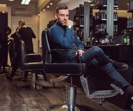 A professional hairdresser sitting on an armchair, has a rest after work with a beer bottle in his hand. stock photos