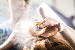 Professional hairdresser styling with hairspray royalty free stock photography