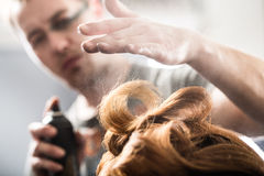 Professional hairdresser styling with hairspray royalty free stock images
