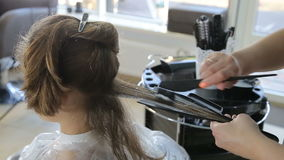 Professional hairdresser, stylist coloring teen girl hair. In white make up room stock footage