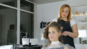 Professional hairdresser, stylist coloring teen girl hair. In white make up room stock video footage
