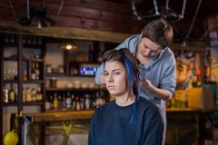 Professional hairdresser doing hairstyle for woman Royalty Free Stock Photos