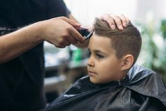 Professional hairdresser uses a hair clipper for fringing hair for a small boy.  royalty free stock images