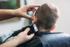 Professional hairdresser uses a hair clipper for fringing hair for a small boy.  stock photos