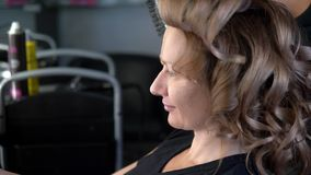 Close-up. Professional hairdresser using curling iron. Hair curls in salon,. Professional hairdresser using curling iron. Hair curls in salon stock video footage