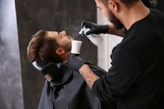 Professional hairdresser using talcum powder to calm client`s skin after shaving. In barbershop royalty free stock photos