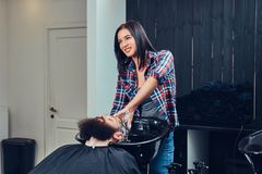 Handsome bearded man in the barbershop. Professional hairdresser washing clients hair in a barbershop royalty free stock images