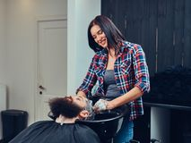 Handsome bearded man in the barbershop. Professional hairdresser washing clients hair in a barbershop royalty free stock photography