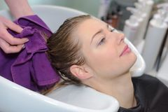 Professional hairdresser washing clients hair. Woman royalty free stock images