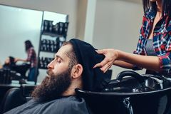 Handsome bearded man in the barbershop. Professional hairdresser wiping with a towel after washing head in a barbershop stock photos