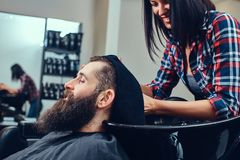 Handsome bearded man in the barbershop. Professional hairdresser wiping with a towel after washing head in a barbershop stock photography