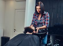 Handsome bearded man in the barbershop. Professional hairdresser wiping with a towel after washing head in a barbershop royalty free stock photo