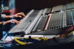 Professional hands nearby soundboard are mixing sounds by audio mixer control panel with buttons and sliders in recording studio royalty free stock images