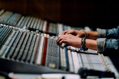 Professional hands nearby soundboard are mixing sounds by audio mixer control panel with buttons and sliders in recording studio stock photography