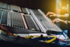 Professional hands with shining warm light nearby soundboard are mixing sounds by audio mixer control panel. Professional hands with shining warm light nearby royalty free stock images