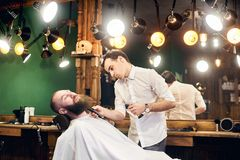 Male client with beard sitting in hairdresser chair. Serious man with long brown beard. Modern popular lumberjack style. stock photo