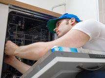 Professional handyman. Professional handyman in overalls repairing domestic dishwasher in the kitchen Royalty Free Stock Photography