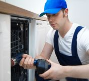 Professional handyman. Professional handyman in overalls repairing domestic dishwasher in the kitchen Stock Image