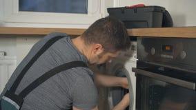 Handyman in overalls repairing washing machine. Professional handyman in overalls repairing washing machine in the kitchen stock footage