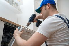 Professional handyman. Professional handyman in overalls repairing domestic dishwasher in the kitchen Royalty Free Stock Images