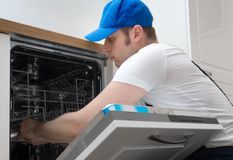 Professional handyman. Professional handyman in overalls repairing domestic dishwasher in the kitchen Royalty Free Stock Image