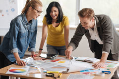 Professional hard working colleagues developing a new design. Creative work. Positive professional hard working colleagues standing around the table and working stock image