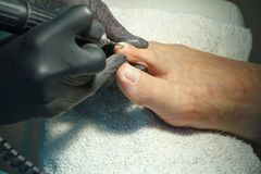 Pedicure master during work. Closeup of female feet and hands in gloves with a special machine tool stock photos