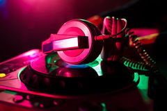 Professional headphones and mixer DJ for music in nightclub on background color lasers Royalty Free Stock Images