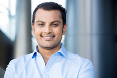 Professional headshot. Closeup headshot portrait, happy handsome business man, smiling, in blue shirt,confident and friendly on office interior background royalty free stock images
