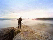Professional hiker and photographer shooting in nature with a digital camera and a tripod. Rocky view point Stock Photo