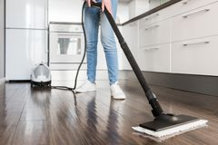 Professional home cleaning service. Woman washes the floor with a steam mop stock image