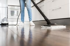 Professional home cleaning service. Woman washes the floor with a steam mop stock photo
