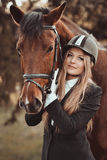 Blondie,beautiful girl with a nice,brown horse in park. Interesting beautiful pretty nice girl with cute and delightful smile.Kind girl with big calm horse Stock Photos