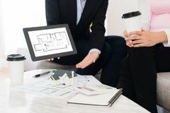 House adviser using mobile digital tablet pad. Professional house adviser women using mobile digital tablet pad showing building plan blueprint document for Stock Images