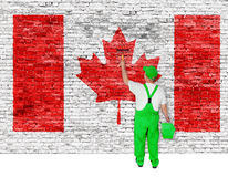 Professional house painter covers wall with flag of Canada. Professional house painter covers brick wall with flag of Canada stock photo