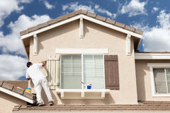 Professional House Painter Painting the Trim And Shutters of A H royalty free stock photography