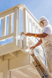 Professional House Painter Wearing Facial Protection Spray Paint. Ing Deck of A Home Royalty Free Stock Images