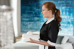 Professional housemaid holding towels Stock Photo